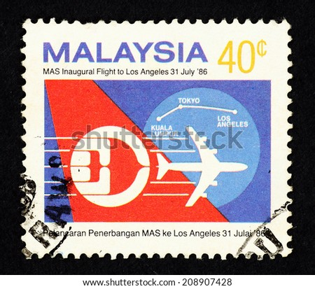 MALAYSIA - CIRCA 1986: Postage stamp printed in Malaysia with image of Malaysia Airlines emblem against an airplane silhouette to commemorate MAS inaugural flight from Kuala Lumpur to Los Angeles. - stock photo