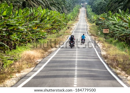 MALAYSIA - December 7, 2013: An open road in Malaysia with moped riders surrounded by palm tree plantations and agriculture. - stock photo