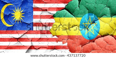 Malaysia flag with Ethiopia flag on a grunge cracked wall - stock photo