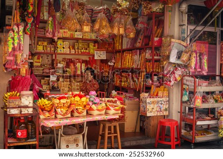 MALAYSIA, PENANG, GEORGETOWN - CIRCA JUL 2014: Elderly woman selling fireworks from a vendor's stall at a local market. - stock photo