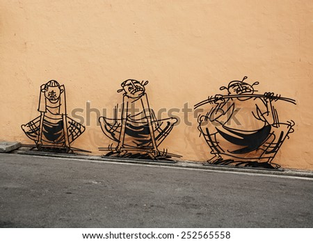 MALAYSIA, PENANG, GEORGETOWN - CIRCA JUL 2014: three dimensional wall art depicting a cartoon style man lifting weights. - stock photo