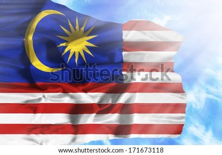 Malaysia waving flag against blue sky with sunrays - stock photo