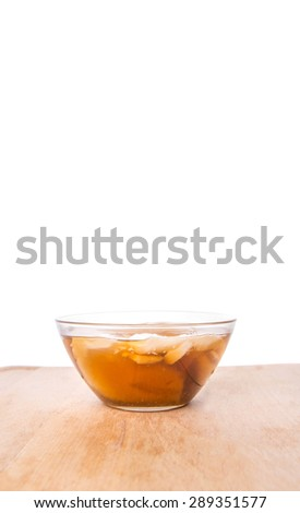 Malaysian dessert dish Tau Fu Fah or soy bean custard mix with brown sugar syrup in clear bowl over wooden background