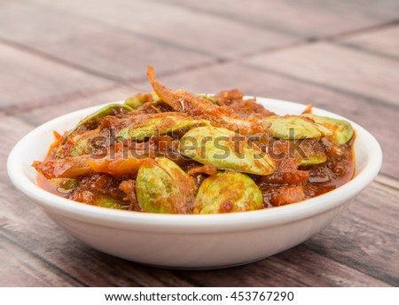 Malaysian dish dried anchovy with stink bean in hot chili sauce or locally known as sambal petai ikan bilis in white bowl over wooden background