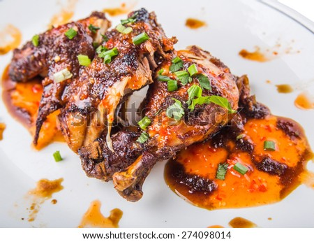 Malaysian dish of roasted chicken pieces coated with soy sauce and chili sauce on white plate - stock photo