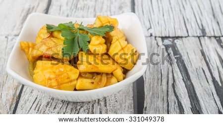 Malaysian dish stir fried squid with parsley leaves in white bowl over wooden background
