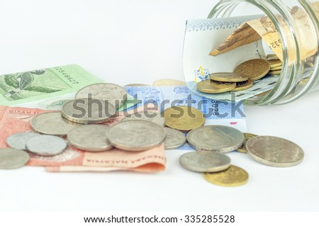 Malaysian Ringgit coins and Notes spilling out of jar