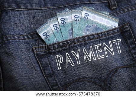 Malaysian ringgit notes sticking out of the blue jeans pocket with word PAYMENT. Business and finance concepts.