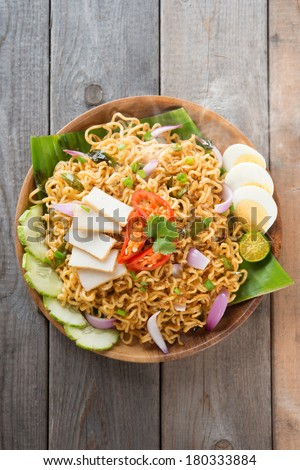 Malaysian style maggi goreng mamak  or spicy dried curry instant noodles.  Asian cuisine, ready to serve on wooden dining table setting. Fresh hot with steamed smoke. - stock photo