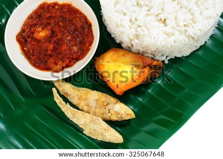 Malaysian traditional food Nasi Lemak served with spicy shrimp gravy, salted fish and fried chicken on banana leaf plate. - stock photo