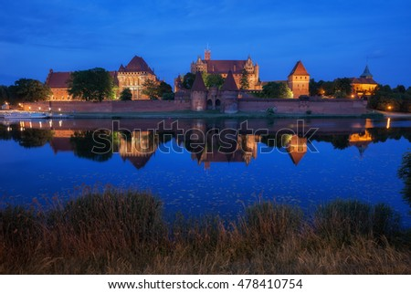 Malbork Castle at night in Poland, Teutonic Knights Order medieval fortress, reflection on Nogat River