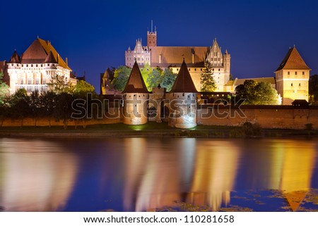 Malbork castle in Poland at night with reflection in Nogat river