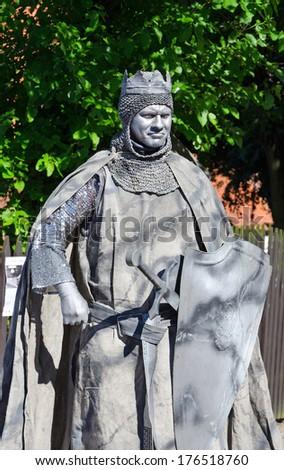 MALBORK - JULY 20, 2013: Street Performer imitating medieval crusader near the Malbork castle in Malbork, Poland on 20 July 2013. - stock photo