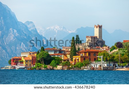 Malcesine town. Ancient tower and fortress in old town malcesine at Garda Lake, Veneto region, Italy. High snowbound top mountains on background summer landscape with colorful houses of Malcesine bank - stock photo