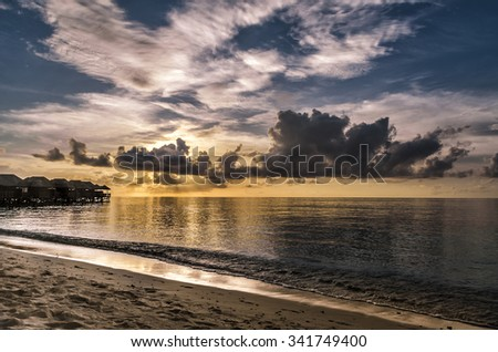 Maldives at sunset. Water bungalows at sunset - stock photo