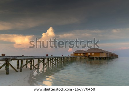 Maldives beach villas in sunset scenery with strong cloud formation - stock photo