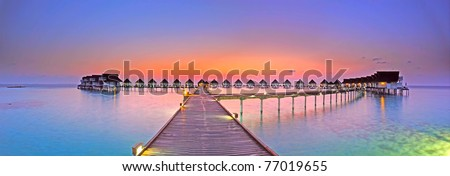 Maldives bungalows sunset panorama - stock photo