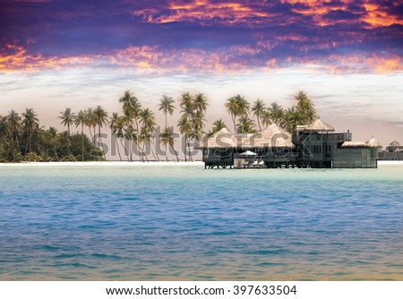 Maldives. houses on piles on water at the time sunset. - stock photo