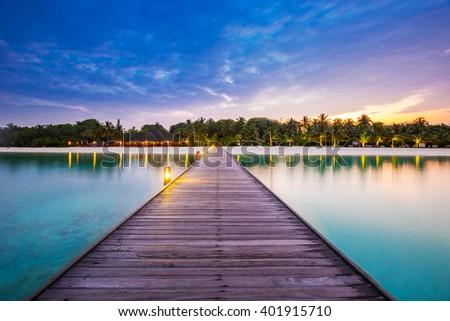 Maldives resort bridge. Beautiful landscape with palms and blue lagoon. - stock photo