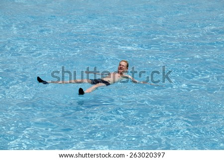 Maldives.  Teenager has a rest on turquoise transparent water of ocean