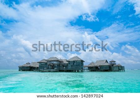 Maldives.Villa on piles on water,Island in ocean - stock photo