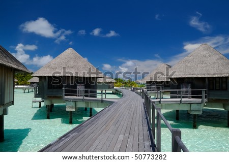 Maldivian water bungalows with blue sky and fresh green sea.