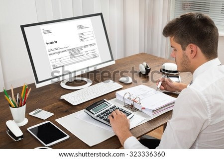 Male Accountant Calculating Tax In Front Of Computer At Desk - stock photo