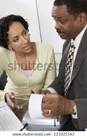 Male accountant with female client discussing at office