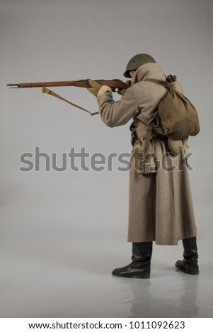 male actor in winter uniform a Russian soldier of the Red Army, a period of 1942 the second world war, posing on a gray background