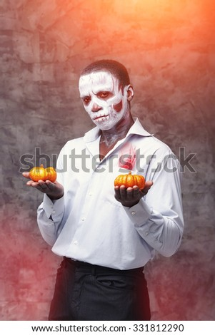 Male african american in the role of a zombie and skeleton. Man is holding two orange pumpkin Halloween holiday symbol. Portrait of an african man - festival, carnival, party, Halloween. Voodoo people - stock photo