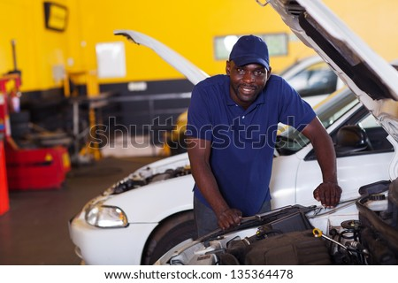 male african car mechanic inside workshop - stock photo