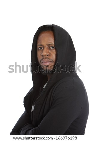 Male African immigrant wearing a black hooded top looking at the camera with a serious resigned expression as he waits for his asylum application to be processed - stock photo
