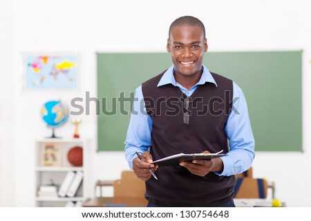 male African school teacher holding a clipboard - stock photo