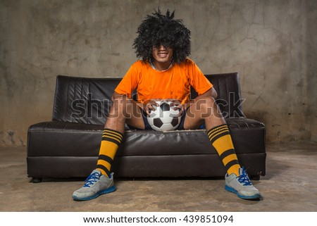 Male afro wig watching a football match on the sofa.