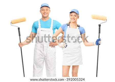 Male and a female decorators holding paint rollers and posing in white uniforms isolated on white background - stock photo