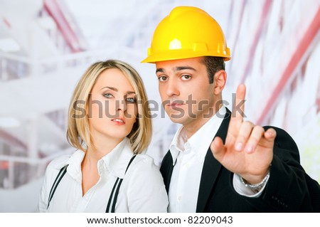 Male and female architects looking at camera, man wearing hardhat and pointing with finger