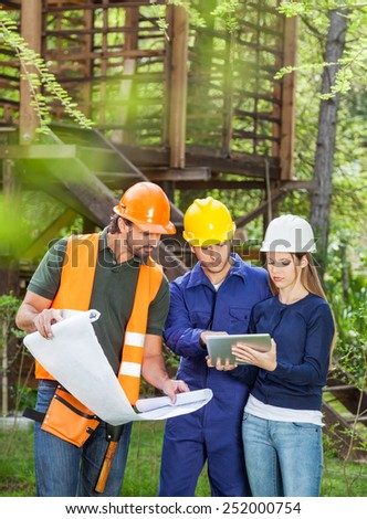 Male and female architects using digital tablet with blueprint at construction site - stock photo