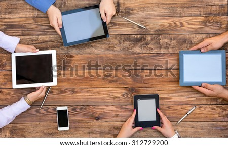 Male and Female Arms with Digital Gadgets. Natural Rough Wooden Plank Desk and Four People Holding Working Electronic Devices Tablet PC Book Notepad Smart Telephone - stock photo