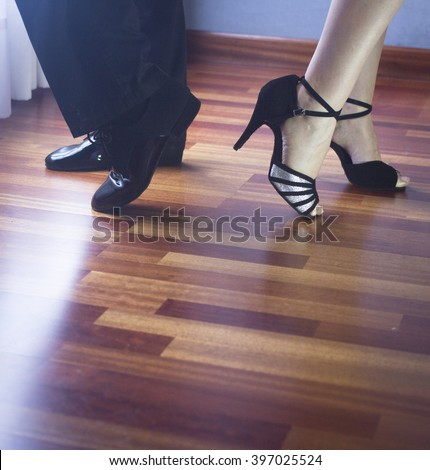 Male and female ballroom, standard, sport dance, latin and salsa couple dancers feet and shoes in dance academy school rehearsal room dancing modern contemporary style.