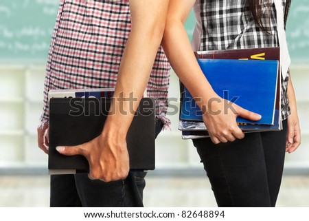 Male and female body part holding book in the classroom - stock photo