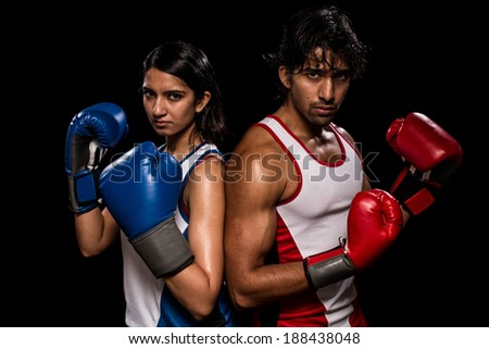 "Male and female boxers ""Battle of the sexes"". Studio shot over black."