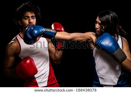 "Male and female boxers ""Battle of the sexes"". Studio shot over black. - stock photo"