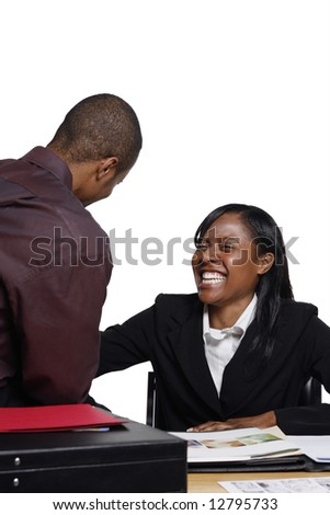 Male and female business colleagues laughing at their desk over a joke. Isolated against a white background. Vertically framed shot.