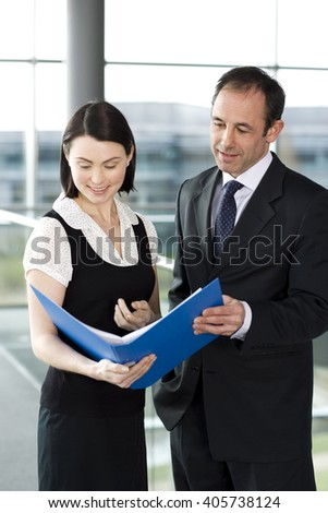Male and female business colleagues looking at notes in a folder - stock photo