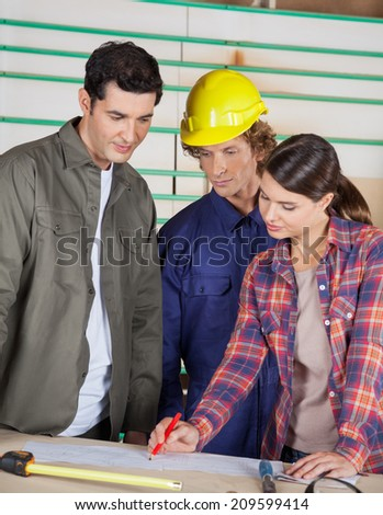 Male and female carpenters discussing over blueprint at table in workshop - stock photo
