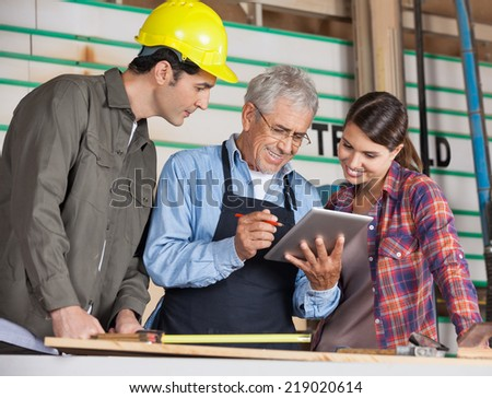 Male and female carpenters using tablet computer in workshop - stock photo