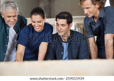 Male and female carpenters working in workshop - stock photo