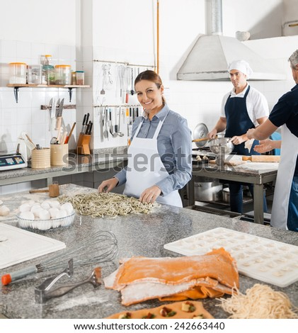 Male and female chefs preparing pasta in commercial kitchen - stock photo