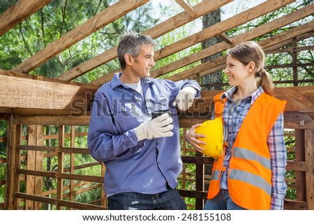 Male and female construction workers looking at each other at site - stock photo