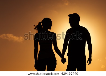 Male and female couple holding hands and looking into each others eyes.